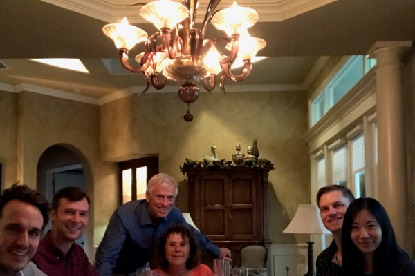 doctor tom stringer and his wife leah hosting uf urology graduating chiefs for dinner. the setting is the dining room of the stringers home. a large chandelier can be seen in the middle of the photo. at the far end of the table is tom stringer and his wife leah. they are dressed in casual clothes. on the left is doctor bergamo dressed in gray scrubs and doctor rabley dress in casual clothes. on the right of the table is doctor kuo and her husband craig. both are dressed in casual clothes.