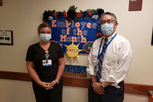 pictured are clinic employee kayla turner urology chairman li-ming su. oceilla is wearig blue scrubs and doctor su is wearing dress pants, dress shirt and tie. the are standing in front of a bulletin board that reads employee of the month. it is decorated in orange and blue. they are both wearing masks.