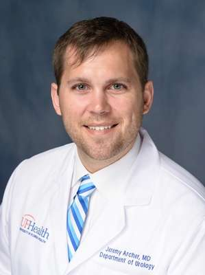 head shot of doctor Jeremy Archer in his white doctor coat. he has on a white shirt with a blue and white striped tie.