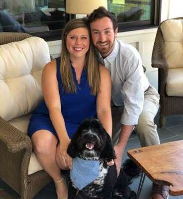 doctor jordan smith and her husband cason in her living room. they are sitting on a cream sofa.. their Portuguese Water Dog named Jefferson is sitting on the floor by their feet.
