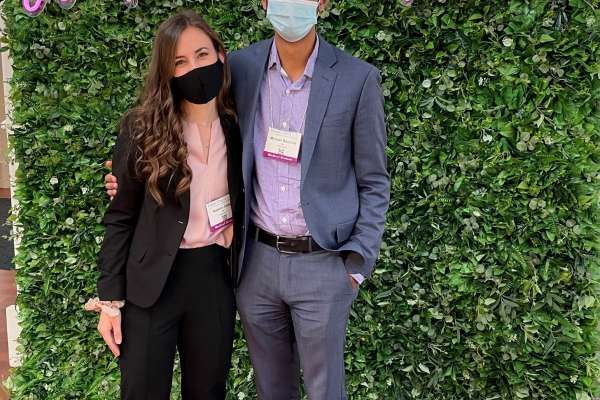 Katelyn Carty (MS4) and Michael Bacchus (MS3) at the Florida Chapter of the American Academy of Pediatrics (FCAAP) The Future of Pediatric Care 2021. they are standing in front of a greenery wall with the words women in pediatrics written in a hot pink color on the greenery.