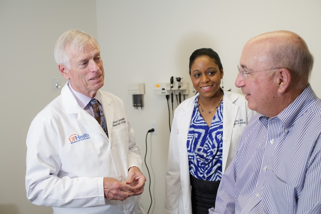 color photo of doctor Thomas F. Stringer and clinic team with adult male patient