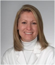 Doctor moody is wearing a white doctor coat with a white turtleneck.  She has shoulder length blond hair.