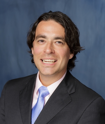 head shot of doctor Benjamin K. Canales wearing a dark gray suit with a pink shirt and light blue and silver tie.