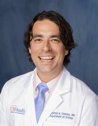 Doctor benjamin canales is a medical doctor. He is wearing his white lab coat with a pink collared shirt and a blue silver tie. He has dark hair. The background of the photo is medium blue.