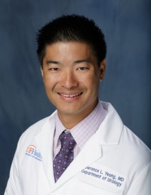 doctor yeung is wearing a pinkish purple collared shirt with a dark purple tie with his white doctors coat. he has dark hair. the background of the photo is medium blue.
