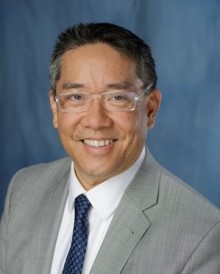 doctor su is wearing gray suit with a white shirt and dark tie. He is wearing glasses with a clear frame.