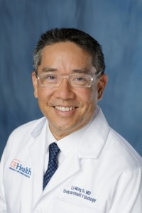 doctor su is wearing a white shirt with a dark blue and black striped tie with his white doctors coat. he is wearing clear framed glasses. he has dark hair. the background of the photo is medium blue.s.