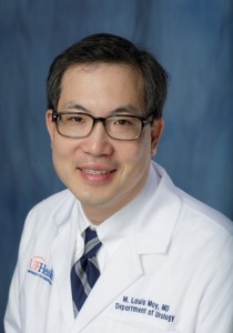 doctor moy is wearing a white doctors coat. he has on a white collared shirt and a dark and light blue multi-striped tie.  he has dark hair and is wearing dark rimmed glasses.  The background of the photo is medium blue.