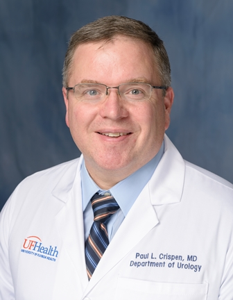 head shot of doctor Paul L. Crispen in a white doctor coat. he has on a blue shirt with a multi striped tie. He has dark blond hair. The background of the photo is medium blue.