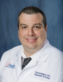 doctor guiterrez is wearing a white doctor coat with a white shirt and black tie with small designs on it.  he has dark hair.  he is a researcher.  the background of the photo is medium blue.
