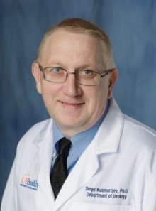 doctor kusmartsev is wearing a white doctors coat. he has on a blue collared shirt and a dark blue tie.  He is in his 30's. he has blond and grey hair. The background of the photo is medium blue.