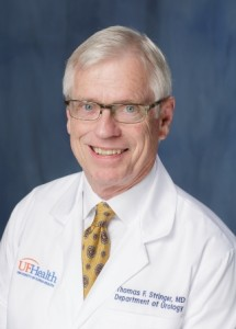 picture of doctor stringer in his white doctors coat. he has on a white collared shirt with gold tie with purple designs.  he has gray hair. he is wearing glasses with a clear type frame.  The background of the photo is medium blue.