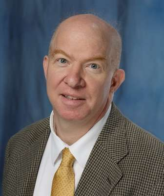 head shot of doctor Vincent G. Bird wearing a brown coat, white shirt and gold tie with small designs on it. He is balding. The background of the photo is a medium blue.