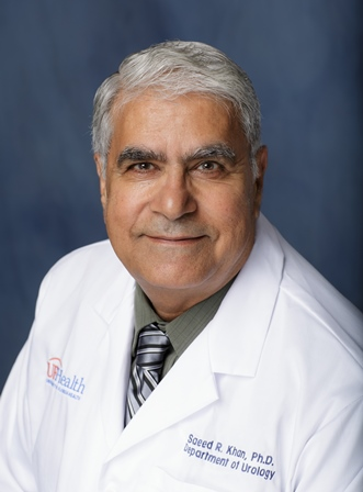 Saeed Khan, PhD is wearing a white doctors coat with a dark gray collared shirt and a grey striped tie.  he has gray hair.  the background of the picture is a dark blue.