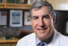 Doctor Scardino is wearing a white doctors coat with a blue shirt and tie.