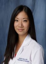 head shot of doctor Jennifer Kuo wearing a white doctors coat with a red dress. the background of the photo is dark blue.