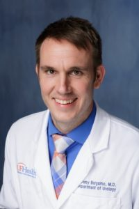 head shot of doctor Jeremy Bergamo wearing a white doctors coat with a blue collard shirt and a white, blue and pink plaid type tie.