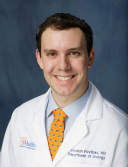 head shot of doctor Jonathan Pavlinec wearing a white doctor coat with a light blue shirt and orange tie with blue dots. He has dark hair and a bright smile