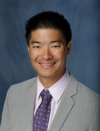 Photo of Doctor Lawrence Yeung who is a medical doctor. He is wearing a grey suit coat a light pink and white checkered collared shirt and a purple, pink and white patterned tie. The background is a fading dark blue.
