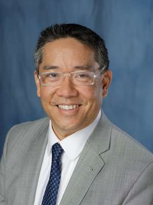 Photo of Doctor Li-Ming Su in a gray suit coat, white collared shirt and dark blue patterned tie. The background is a mix of dark and light blue color.