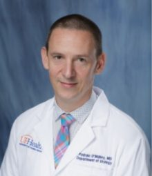 picture of doctor o'malley in his white doctors coat. he has on a white shirt with small blue plaid squares and a multi striped pink and light blue tie.  he has dark brown hair. The background of the photo is medium blue.