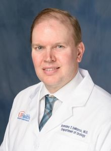 head shot of doctor Romano T. DeMarco wearing a white doctors coat. he has on a white collared shirt and a blue multi-striped tie. He has dark blond hair. The background of the photo is medium blue.
