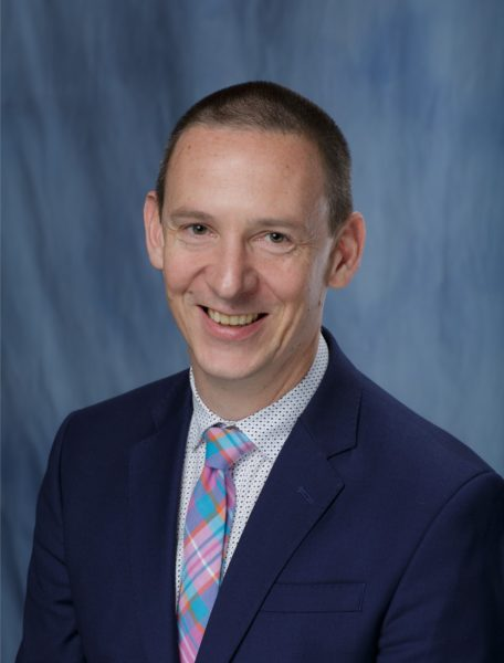doctor o'malley in a dark suit with light blue shirt. his tie is light blue, white and pink.