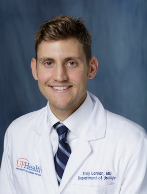 head shot of doctor Troy Larson wearing his white doctor coat, a white shirt and blue striped tie.