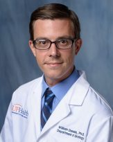 head shot of William L. Donelan, doctor of philosophy wearing a white doctors coat. he has on a blue collared shirt and a light and dark blue stripped tie. He is in his 30's. he has dark hair. he is a researcher. The background of the photo is medium blue.