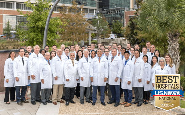 Group photo of the UF urology team. This includes faculty, residents and extenders. They are standing in multiple rows. They are all wearing their white doctor coats. They are standing in front the fountain at the UF Health Shands Cancer hospital. In the top right corner is the US News and World Report badge. This badge is gold with a blue banner across it with the words Best Hospitals US News & World Report National Urology 2020 - 2021.