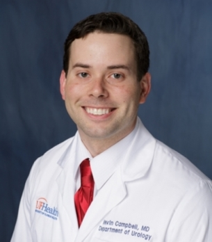 head shot of doctor Kevin Campbell wearing a white doctors coat with a white collared shirt and red tie.