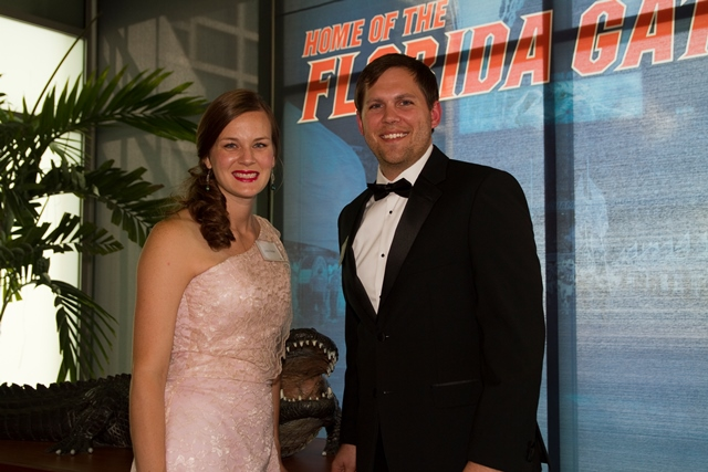 doctor and mrs jeremy archer.  mrs. archer is wearing a white evening gown.  he is wearing a black tux with white shirt and black bow tie.  they are standing near a large bronzed gator statue.  in the background is an orange and blue screen with the words home of the florida gators in orange.