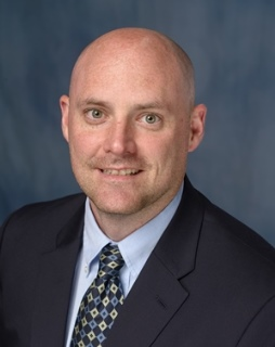 head shot of doctor James B. Mason wearing a dark blue suit with a lighter blue collared shirt and tie. the tie has silver and blue diamond shaped designs. the background of the picture is a medium to dark shaded blue.