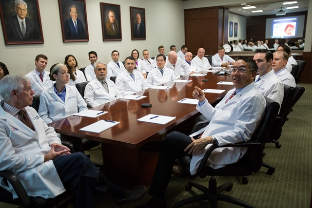 uf urology faculty and residents in the urology conference room.  they are all wearing white doctor coats and seated around the table and around the room.  the room has cream walls with oil portraits hanging on the wall.  the table and cabinets are a dark colored wood.