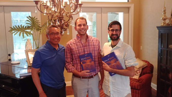 doctors su, ashouri and batra.  they are standing in the dining room.  doctors ashouri and batra are holding books given to them by doctor su.