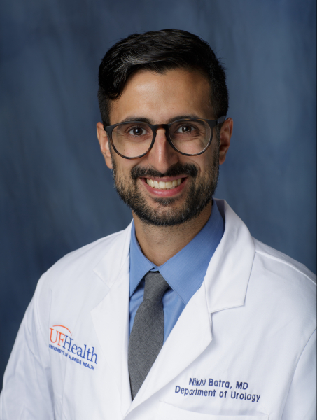 doctor batra is wearing his white doctors coat with a blue shirt and dark grey tie. He has a black beard and mustache. He is wearing dark framed glasses.