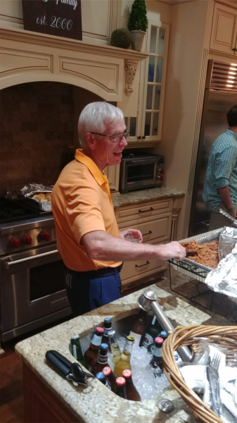 doctor stringer getting ready to eat some bbq.  he is in the kitchen.  he is wearing an orange polo shirt and blue shorts.  he is laughing.