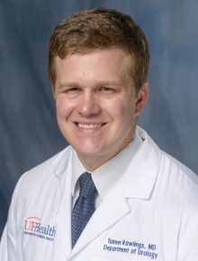doctor tanner rawlings is wearing his white doctors coat. he is wearing a white shirt with a blue tie.