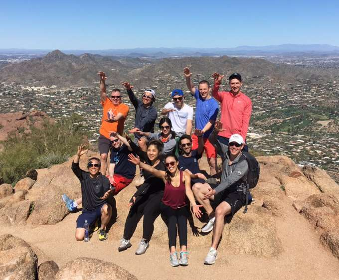 Some of uf urology faculty, residents and alumni on top of camelback mountain in arizona after hiking to the top. They are all dressed in workout type clothes (tshirts, shorts, long sleeve shirts, leggings and athletic shoes. They are all laughing and smiling and doing the gator chomp. The mountain is a tan color and the background is a beautiful clear blue sky and views of other mountains.