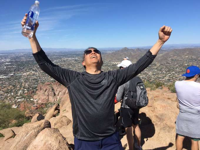 doctor Su after climbing to the top of camelback mountain after a hike.  his arms are raise in celebration.  the background of the photo shows the mountain range and a blue sky.