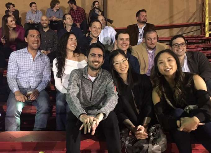 uf urology faculty and residents at rodeo event at the sesaua.  they are sitting in the stands laughing and talking.