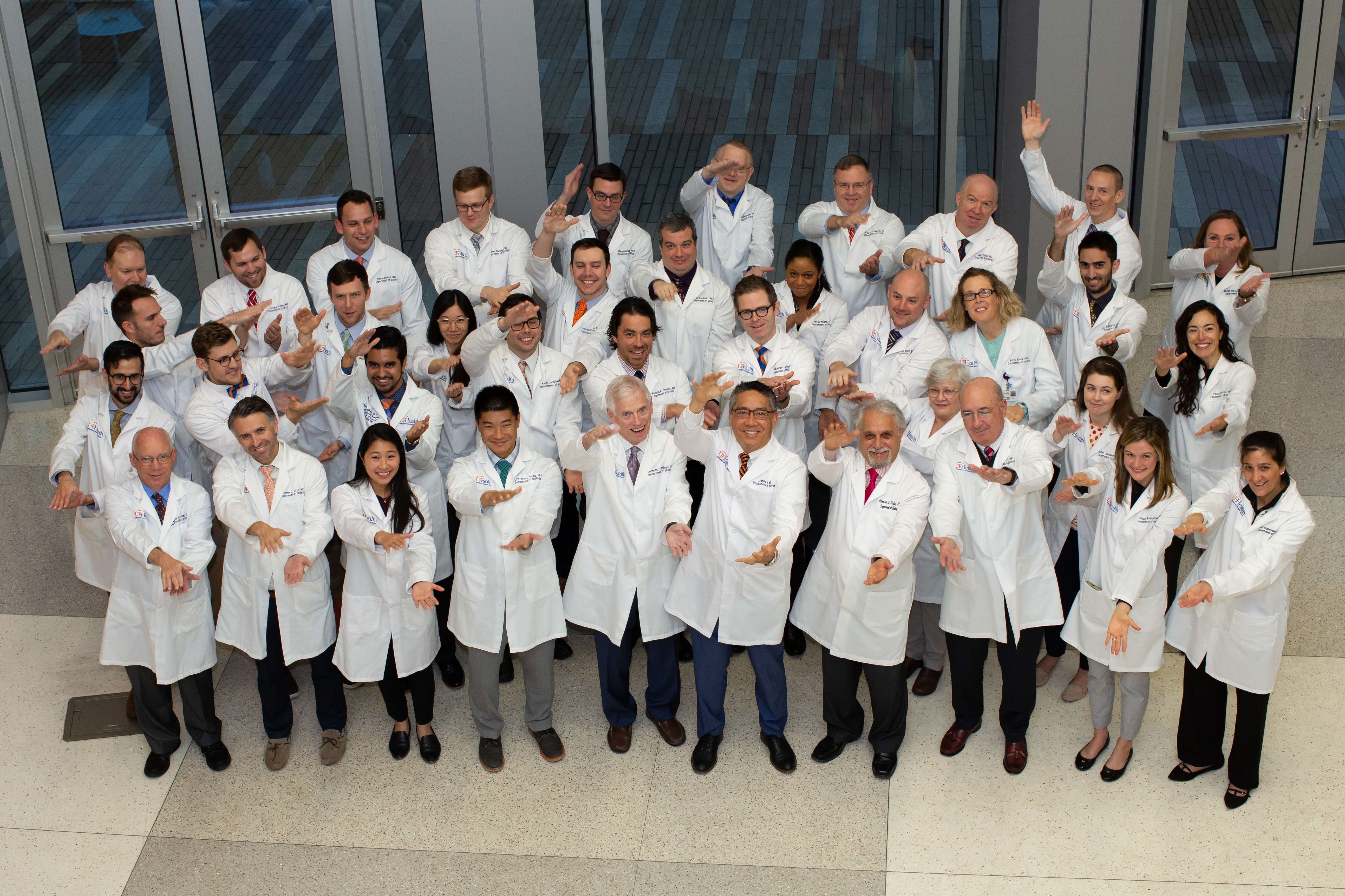 group picture of uf health urology faculty doing the gator chomp