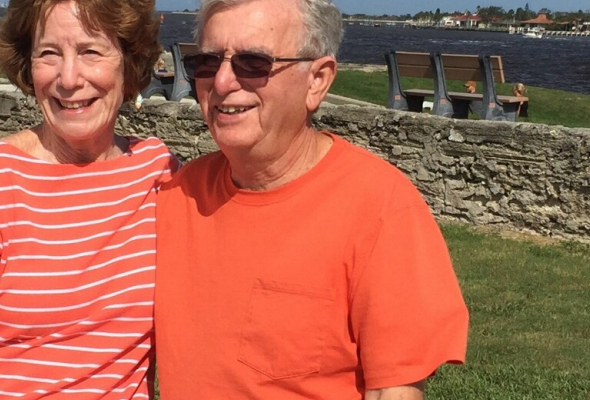 picture of susan baglivio and a relative. they are standing with their arms around each other. They are both smiling. the background is the fort at st augustine. its a brick half wall with water far in the background.
