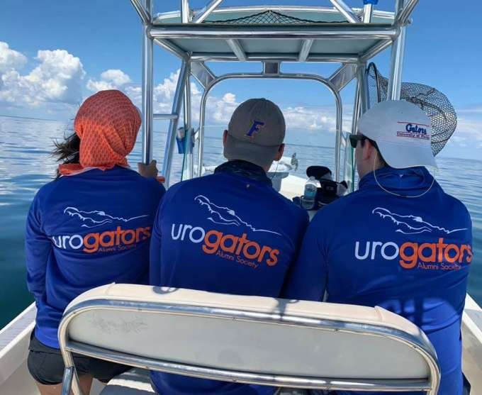 doctors han, pavlinec and noennig are sitting on a bench on doctor su's boat.  theya are facing away from the camera.  they are wearing gator blue long sleeve shirts with the words and logo urogators on the back.  the sky is blue and has white puffy clouds.