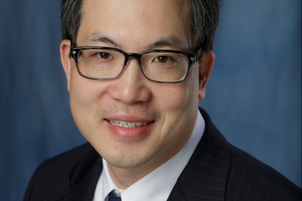 Headshot of Lou Moy who is a medical doctor. He is wearing a black pin stripped suit jacket with a white collared shirt and a dark and light blue striped tie. He has dark hair and is wearing black framed glasses. The background of the photo is blue.