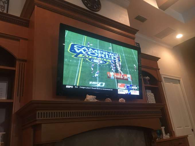 large tv above the fireplace in the home of the su's.  uf urology residents, faculty and family are watching the uf vs miami football game.