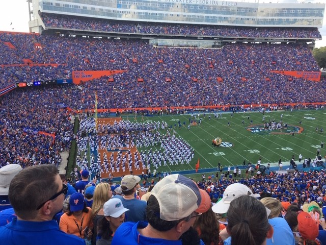 a photo taken from midway of the stadium. the crowd is for the most part wearing orange and blue. the football field is a gorgeous green. the uf band is on the field forming a u and a f.