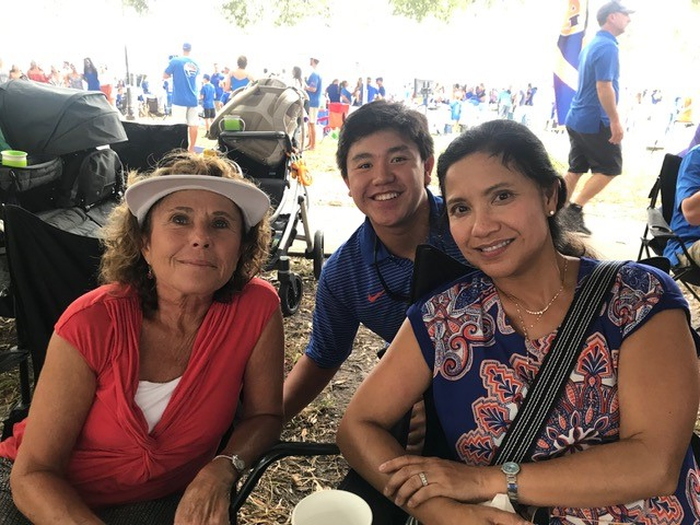 leah stringer, maria and sean su. they are seated under the tailgate tent.