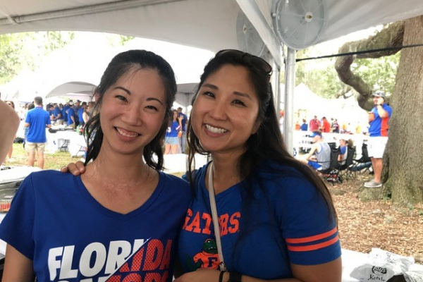 doctors han and kuo. they are laughing and smiling. they are wearing florida gator tshirts and holding orange and blue poms.